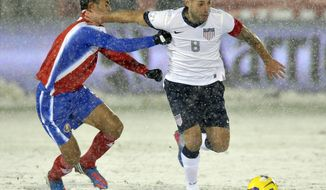 Costa Rica defender Giancarlo Gonzalez, left, pulls the jersey of United States forward Clint Dempsey (8) during the first half of a World Cup qualifier soccer match in Commerce City, Colo., Friday, March 22, 2013. (AP Photo/Jack Dempsey)