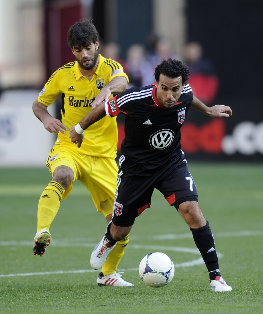 Columbus Crew defender/midfielder Agustin Viana, left, fights for the ball against D.C. United midfielder Dwayne De Rosario (7) during the second half of an MLS soccer game on Saturday, March 23, 2013, in Washington. Columbus won 2-1. (AP Photo/Nick Wass)