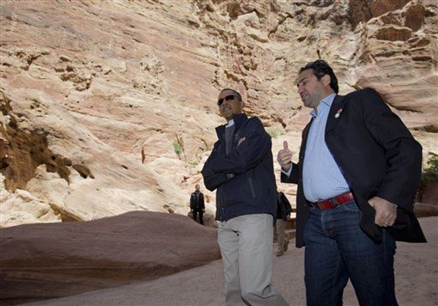 U.S. President Barack Obama, left, with Dr. Suleiman A.D. Al Farajat, a tourism professor with the University of Jordan, walks from the Ancient Shrine, at right, in the Siq during a visit to the ancient city of Petra, in south Jordan, Saturday, March 23, 2013. (AP Photo/Carolyn Kaster)