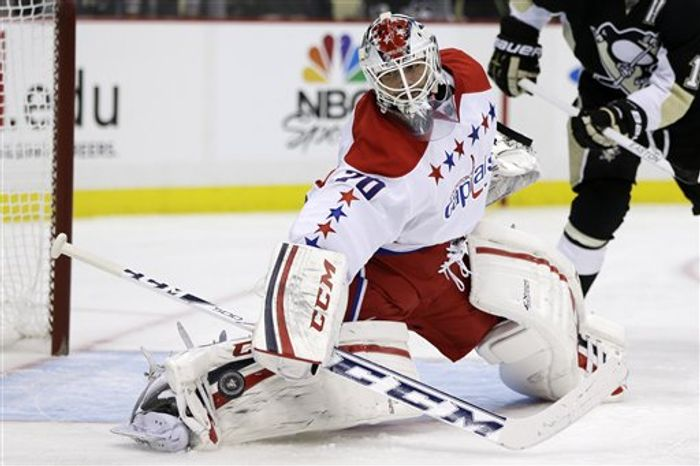 Washington Capitals goalie Braden Holtby (70) blocks a shot during the second period of an NHL hockey game against the Pittsburgh Penguins in Pittsburgh Tuesday, March 19, 2013. The Penguins won 2-1. (AP Photo/Gene J. Puskar)