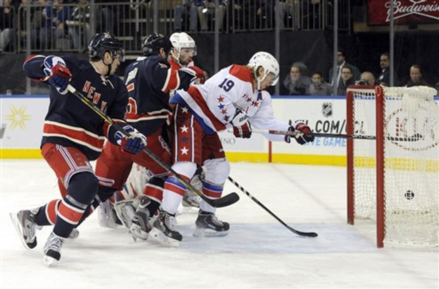 Washington Capitals' Nicklas Backstrom (19), of Sweden, scores a goal as New York Rangers' Ryan McDonough, left, and Dan Girardi look on during the first period of an NHL hockey game Sunday, March 24, 2013, at Madison Square Garden in New York. (AP Photo/Bill Kostroun)