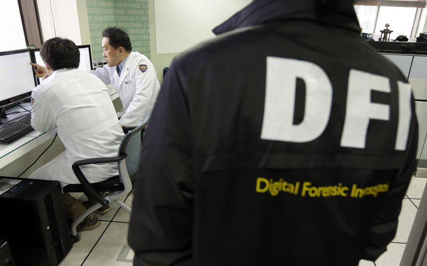 South Korean computer researchers (left) check the computer servers of the Korean Broadcasting System as a South Korean police officer from Digital Forensic Investigation watches at the Cyber Terror Response Center at the National Police Agency in Seoul on Thursday, March 21, 2013. (AP Photo/Lee Jin-man)
