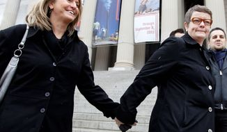 Sandy Stier (left) and Kris Perry of Berkeley, Calif., hold hands Monday by the National Archives. Tens of thousands of gay-marriage advocates and opponents are expected to be in the District this week. (Associated Press)