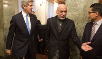 U.S. Secretary of State John F. Kerry (left) walks to a meeting with Afghan President Hamid Karzai (center) at the Presidential Palace in Kabul, Afghanistan, on Monday, March 25, 2013. (AP Photo/Jason Reed, Pool)
