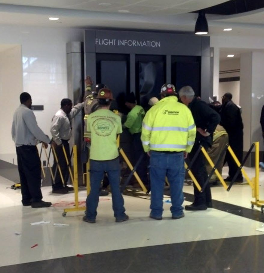 Workers hold up a flight information sign that fell on a family and killed a child in the terminal at the Birmingham-Shuttlesworth International Airport in Birmingham, Ala., on Friday, March 22, 2013. The mother and two other children were injured. (AP Photo/AL.com, Carol Robinson).