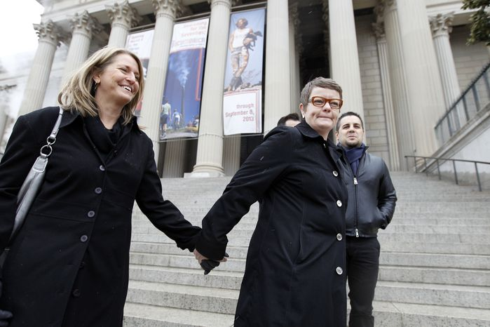 Sandy Stier (left) and Kris Perry of Berkeley, Calif., stand outside the National Archives in Washington on March 25, 2013, before going inside to view the U.S. Constitution, a day before their same-sex marriage case is argued before the Supreme Court. (Associated Press)