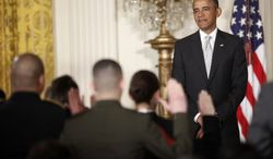 President Obama, watches as the Oath of Allegiance is administered at a naturalization ceremony for active duty service members and civilians in the East Room of the White House in Washington on March 25, 2013. (Associated Press)