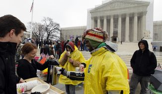 Jeff Thomson (left) and Kelsi Browning hands out free coffee to people who wait outside of the U.S. Supreme Court in Washington on March, 25, 2013, a day before the case for gay and lesbian couples rights, will be argued before the Supreme Court. (Associated Press)