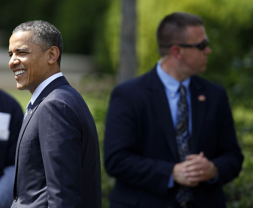 **FILE** President Obama (left) walks past a Secret Service agent after welcoming the NCAA college football BCS National Champion University of Alabama Crimson Tide to the South Lawn of the White House to honor their 14th championship on April 19, 2012, in Washington. (Associated Press)