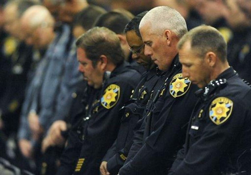 Law enforcement officers bow their head during the memorial of Tom Clements. The public memorial for the chief executive of the Department of Corrections was held at New Life Church in Colorado Springs, Colo., on Monday, March 25, 2013. Tom Clements was shot and killed on the doorstep of his home last week in Monument, Colorado (AP Photo/The Gazette, Jerilee Bennett, Pool)