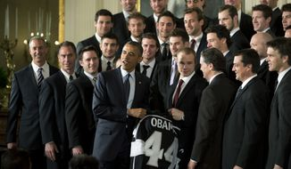 President Barack Obama poses with Los Angeles Kings hockey team during a ceremony in the East Room of the White House in Washington, Tuesday, March 26, 2013, where he honored the 2012 Stanley Cup hockey champions and the Major League Soccer champions LA Galaxy. (AP Photo/Manuel Balce Ceneta)