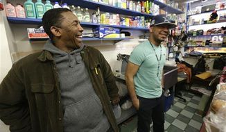 Casiano Quezada, right, talks to an unidentified friend inside Apple Deli Grocery, Tuesday, March 26, 2013, in Passaic, N.J. Quezada is the son of Pedro Quezada, 44, who won the $338 million Powerball jackpot after purchasing the winning ticket at Eagle Liquors store in Passaic. (AP Photo/Julio Cortez)