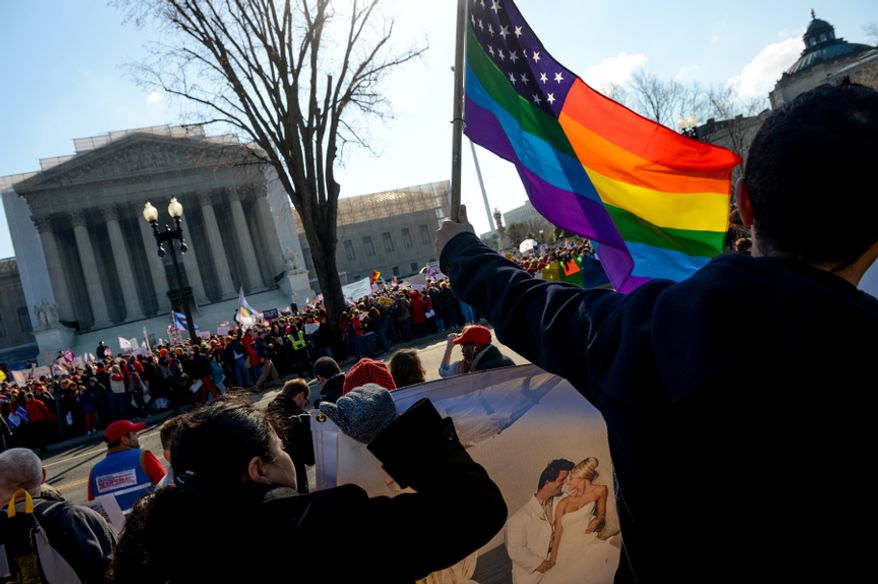 Franco Ciammachilli (right) of Washington waves a rainbow flag, a symbol of gay pride, behind supporters of traditional marriage outside the U.S. Supreme Court in Washington as the justices began hearing two days of arguments in cases involving gay marriage on March 26, 2013. (Andrew Harnik/The Washington Times) **FILE**