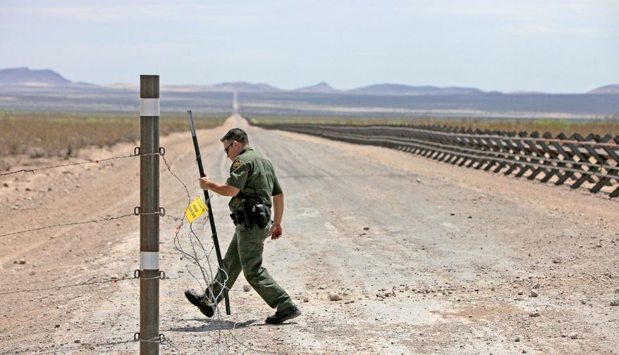 ** FILE ** A road lined with vehicle barriers marking the U.S-Mexico border in New Mexico is the spartan territory for Border Patrol agents. (Associated Press)
