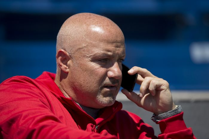 Washington Nationals GM Mike Rizzo talks on the phone before the start of an exhibition spring training baseball game against the Atlanta Braves on Wednesday, March 27, 2013, in Viera, Fla. (AP Photo/Evan Vuc