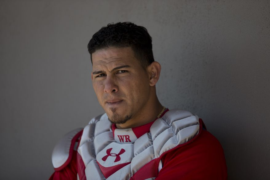 Washington Nationals catcher Wilson Ramos sits in the dugout before the start of an exhibition spring training baseball game against the Atlanta Braves on Wednesday, March 27, 2013, in Viera, Fla. (AP Photo/Evan Vucci)