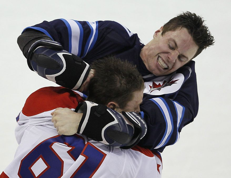 Winnipeg Jets' James Wright, rear, and Washington Capitals' Steve Oleksy (61) fight during the first period of an NHL hockey game in Winnipeg, Manitoba, on Thursday, March 21, 2013. (AP Photo/The Canadian Press, John Woods)