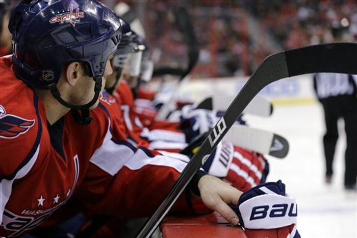 Washington Capitals center Brooks Laich (21), left, and others rest on the bench during a timeout in the first period of an NHL hockey game aga