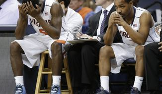 Virginia guards Teven Jones (5) and Jontel Evans (1) watch their team during the second half of an NIT college basketball game against Virginia in Charlottesville, Va., Wednesday, March 27, 2013. Iowa won 75-64. (AP Photo/Steve Helber)