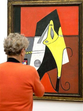 "A visitor looks at the painting ""Femme dans un fauteuil"" (1927) by Spanish painter Pablo Picasso (1881-1973) in the Kunstmuseum, the art museum, in Basel, Switzerland, on Friday, March 15, 2013. (Associated Press)"