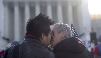 Wyatt Tan (left) and Mark Nomadiou, both of New York City, kiss in front of the Supreme Court in Washington on Wednesday, March 27, 2013, before the start of a court hearing on the 1996 Defense of Marriage Act (DOMA). In the second of back-to-back gay-marriage cases, the high court is turning to a constitutional challenge to the law that prevents legally married gay Americans from collecting federal benefits generally available to straight married couples. (AP Photo/Carolyn Kaster)