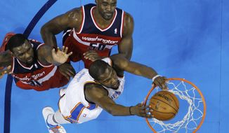 Oklahoma City Thunder forward Kevin Durant dunks in front of Washington Wizards center Emeka Okafor (50) and forward Chris Singleton (31) in the first quarter of an NBA basketball game in Oklahoma City, Wednesday, March 27, 2013. Oklahoma City won 103-80. (AP Photo/Sue Ogrocki)