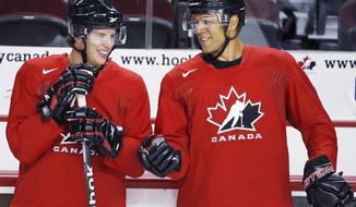 **FILE** Sidney Crosby, left, and Jarome Iginla, chat during a practice at the Men's National Olympic Hockey Team orientation camp in Calgary, Tuesday, Aug. 25, 2009. The Calgary Flames Hockey Club have traded team captain Jarome Iginla in exchange for forwards Kenneth Agostino and Ben Hanowski and the Pittsburgh Penguins 2013 first round pick. (AP Photo/The Canadian Press, Fred Chartrand, file)