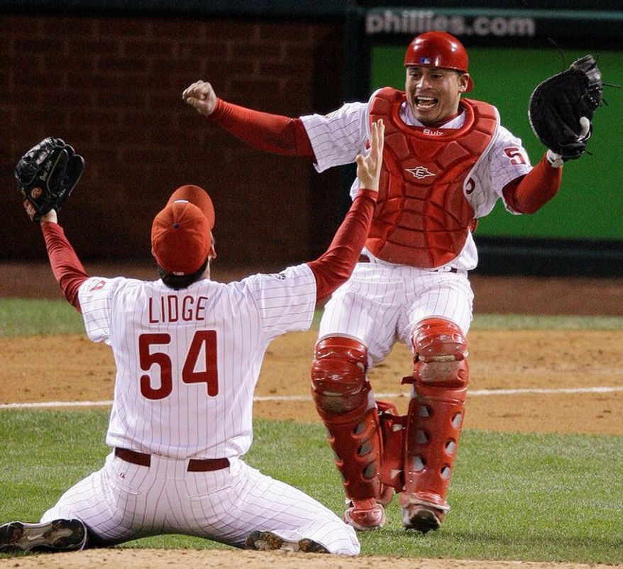 Phillies catcher Carlos Ruiz rushes to the mound to celebrate with closer Brad Lidge after Philadelphia defeated Tampa Bay in Game 5 of the 2008 World Series to win the franchise's first title in 28 seasons. (Associated Press)