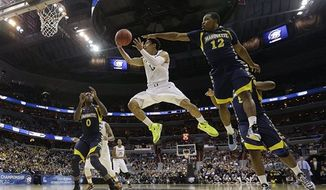Miami guard Shane Larkin (0) elevates toward the basket under pressure from Marquette guard Derrick Wilson (12) as forward Jamil Wilson (0) watches during the second half of an East Regional semifinal in the NCAA college basketball tournament, Thursday, March 28, 2013, in Washington. (AP Photo/Pablo Martinez Monsivais)