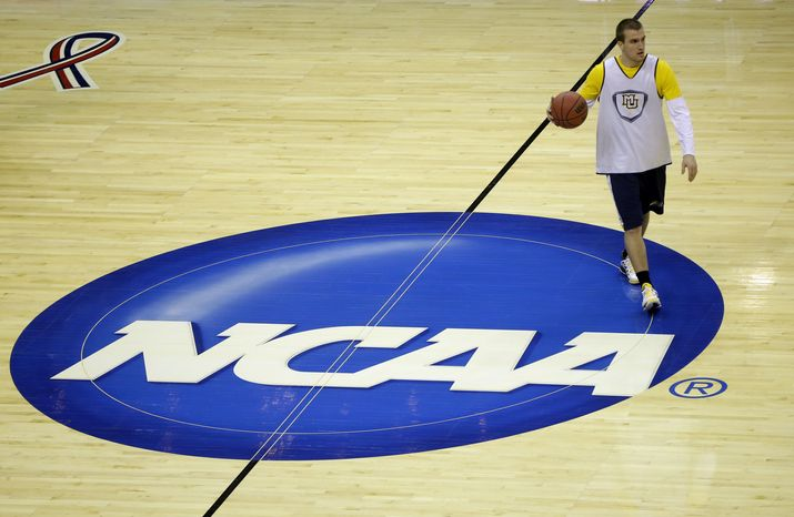 Marquette guard Jake Thomas moves over the NCAA logo during practice for a regional semifinal game in the NCAA college basketball tournament, Wednesday, March 27, 2013, in Washington. Mar