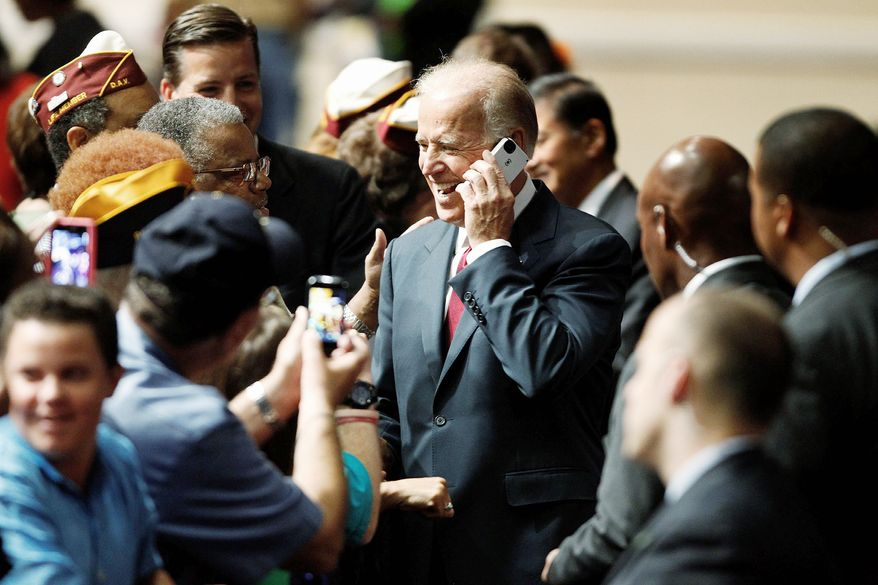 **FILE** Vice President Joseph R. Biden speaks on a cell phone from a member of the audience at the Disabled American Veterans National Convention in Las Vegas on Aug. 4, 2012. (Associated Press/Las Vegas Review-Journal)