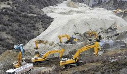 In this photo released by China's Xinhua News Agency, earthmovers remove rocks and mud on the scene where a landslide hit a mining area in Maizhokunggar County of Lhasa, southwest China's Tibet Autonomous Region, on March 29, 2013. The large landslide trapped dozens of workers in the gold mining area, state media reported. (Associated Press/Xinhua)
