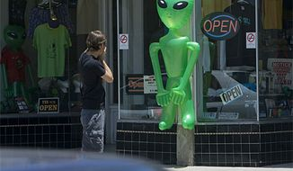 ** FILE ** A tourist photographs an alien outside a T-shirt and souvenir shop in Roswell, N.M., in 2007. (Associated Press)