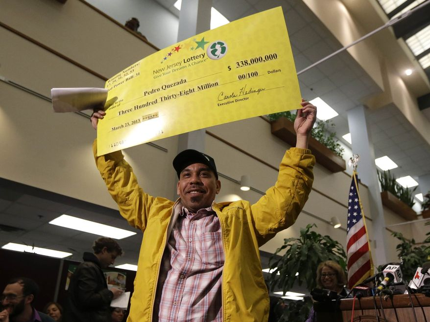 Pedro Quezada, the winner of the Powerball jackpot, holds up a promotional check during a news conference at the New Jersey Lottery headquarters, Tuesday, March 26, 2013, in Lawrenceville, N.J. Quezada , 45, won the $338 million jackpot with the winning ticket he purchased at Eagle Liquors store in Passaic, N.J. (AP Photo/Julio Cortez)