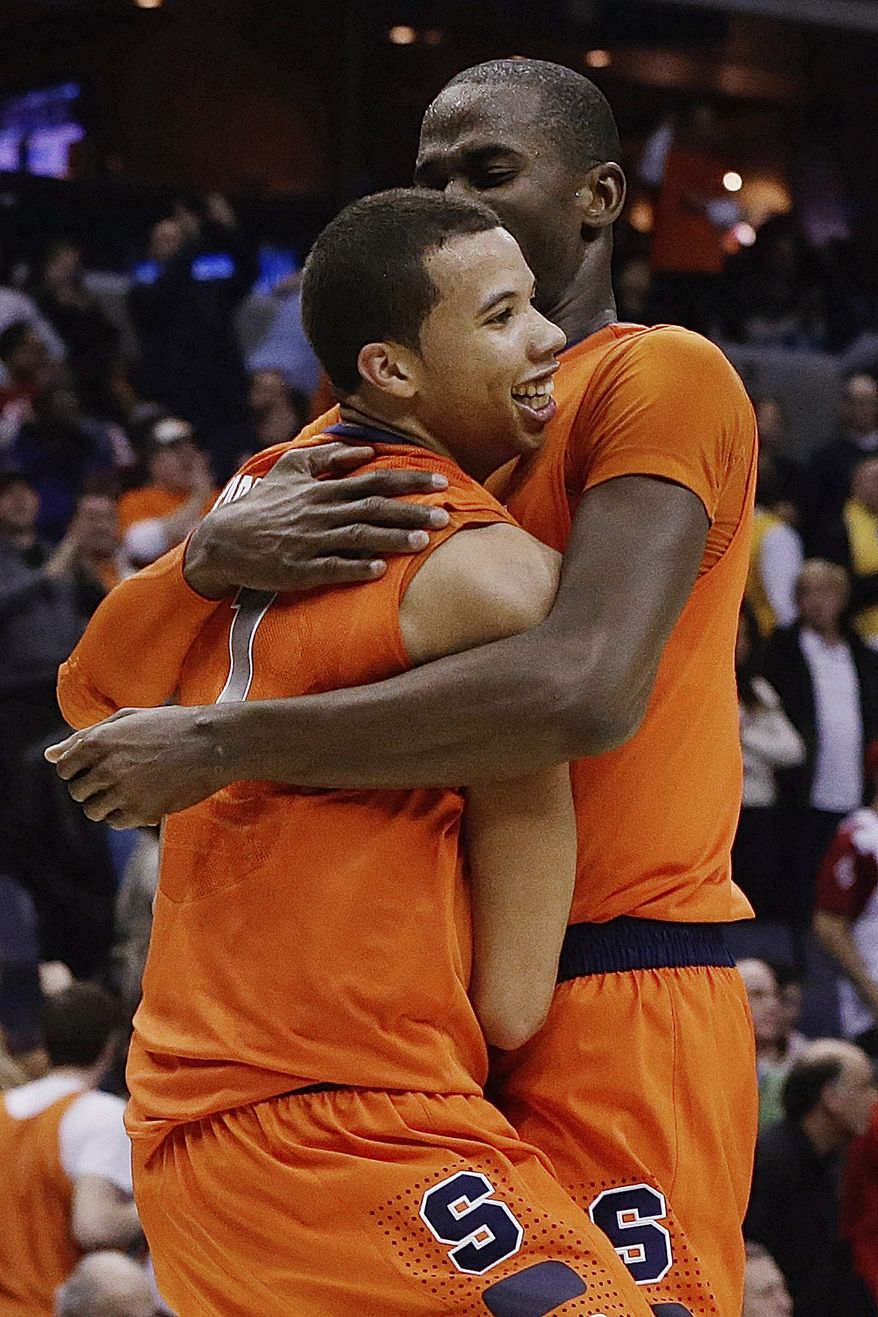 Syracuse guard Michael Carter-Williams (1) is hugged by center Baye Keita (12) after an East Regional semifinal against Indiana in the NCAA men's college basketball tournament, Thursday, March 28, 2013 in Washington. Syracuse defeated Indiana 61-50. (AP Photo/Pablo Martinez Monsivais)