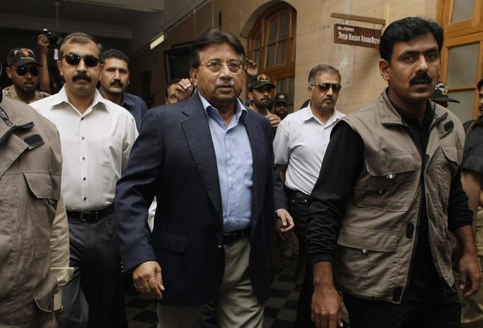 ** FILE ** Former Pakistani President Pervez Musharraf, center, surrounded by guards arrives in a court in Karachi, Pakistan on Friday, March 29, 2013. (AP Phot