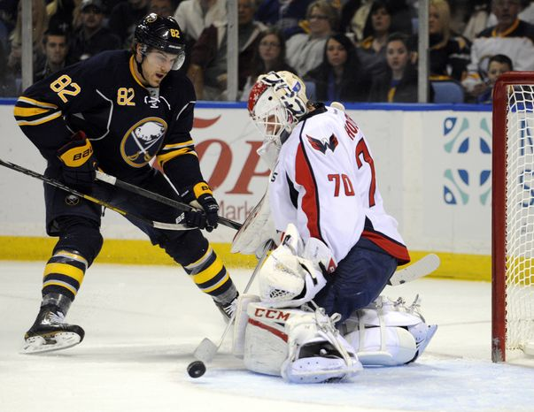 Buffalo Sabres left winger Marcus Foligno (82) deflects the puck as Washington Capitals goaltender Braden Holtby (70) turns the shot away during the first period of an NHL hockey game in Buffalo, N.Y., Saturday, March 30, 2013. (AP Photo/Gary Wiepert)