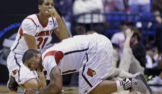 Louisville's Chane Behanan, foreground, and Wayne Blackshear (20) react to guard Kevin Ware's injury during the first half of the Midwest Regional final against Duke in the NCAA college basketball tournament, Sunday, March 31, 2013, in Indianapolis. (AP Photo/Michael Conroy)