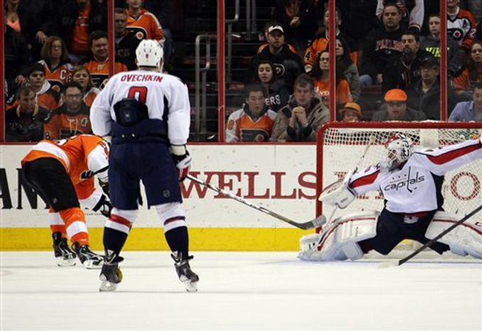Philadelphia Flyers' Ruslan Fedotenko, far left, scores the winning goal past Washington Capital goalie Braden Holtby, right, as Alex Ovechkin, center, watches in overtime of an NHL hockey game, Sunday, March 31, 2013, in Philadelphia. The Flyers won 5-4. (AP Photo/Tom Mihalek)