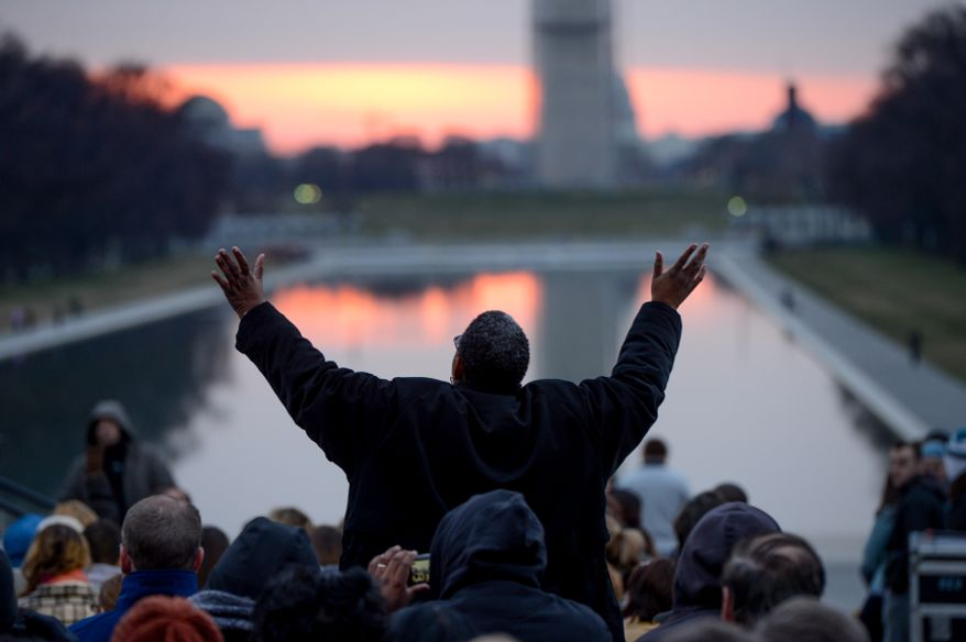 Kim Arnold of Sterling, Va., reacts in the crowd during a religious song at the 35th annual Easter Sunrise Service at the Lincoln Memorial in Washington on Sunday, March 31, 2013. (Andrew Harnik/The Washington Times)