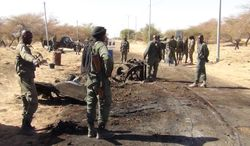 ** FILE ** Malian soldiers stand around the debris left after a jihadist suicide bomber blew himself up at a Malian army checkpoint near the airport in Timbuktu, Mali, on Thursday, March 21, 2013. (AP Photo)