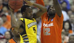 Marquette guard Junior Cadougan (5) passes around Syracuse center Baye Keita (12) during the second half of the East Regional final in the NCAA men's college basketball tournament, Saturday, March 30, 2013 in Washington. (AP Photo/Pablo Martinez Monsivais)