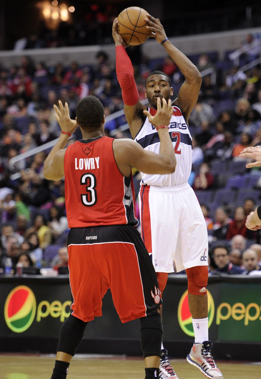 Washington Wizards guard John Wall (2) looks to pass against Toronto Raptors guard Kyle Lowry (3) during the second half of an NBA basketball game, Sunday, March 31, 2013, in Washington. The Wizards won 109-92. (AP Photo/Nick Wass)