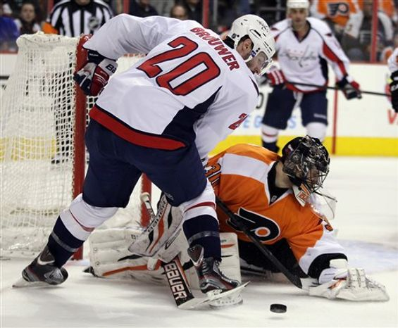 Washington Capital's Troy Brouwer, left, tries to get the puck swept aside by Philadelphia Flyers' Ilya Bryzgalov during a five-on-three Washington power play in the first period of an NHL hockey game, Sunday, March 31, 2013, in Philadelphia. (AP Photo/Tom Mihalek)