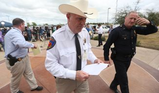 Kaufman County Sheriff David Byrnes, center, walks away after a news conference in Kaufman, Texas, on Sunday March 31, 2013. On Saturday, Kaufman County District Attorney Mike McLelland and his wife, Cynthia, were killed in their home. (AP Photo/Mike Fuentes)