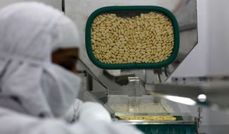 ** FILE ** In this Thursday, Feb. 9, 2012, file photo, a pharmacist works in a lab where medicines are being produced at a Cipla manufacturing unit on the outskirts of Mumbai, India. A lawyer for healthcare activists says India's Supreme Court has rejected drug maker Novartis AG' right to patent a new version of a lifesaving cancer drug. (AP Photo/Rafiq Maqbool, File)