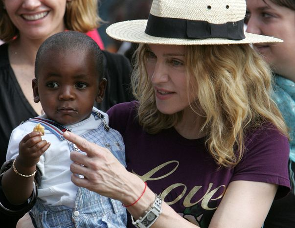 ** FILE ** The American pop singer Madonna carries David Banda, her Malawian adopted son, at Consol Homes, a day care center that she funds in