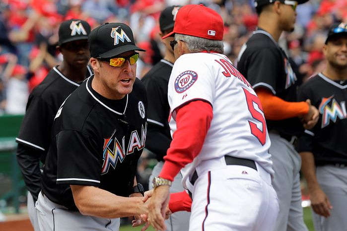 Washington Nationals manager Davey Johnson (5) greets Miami Marlins manager Mike Redmond (11) before the opening day baseball game in Washington, on Monday, April 1, 2013.  (AP Photo/Alex Brandon)