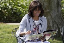 """First lady Michelle Obama reads the book """"Cloudy With A Chance of Meatballs"""" to children as part of the annual White House Easter Egg Roll, Monday, April 1, 2013, on the South Lawn of the White House in Washington. (AP Photo/Jacquelyn Martin)"""