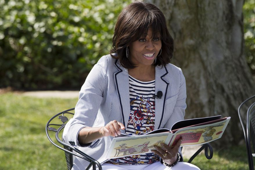 "First lady Michelle Obama reads the book ""Cloudy With A Chance of Meatballs"" to children as part of the annual White House Easter Egg Roll, Monday, April 1, 2013, on the South Lawn of the White House in Washington. (AP Photo/Jacquelyn Martin)"